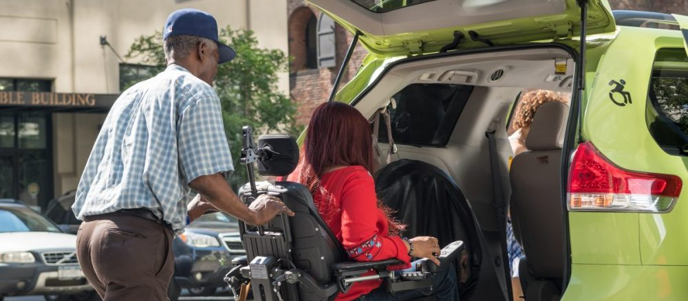 A taxi driver assists a woman who uses a motorized wheelchair into the back of a wheelchair accessible green taxi.