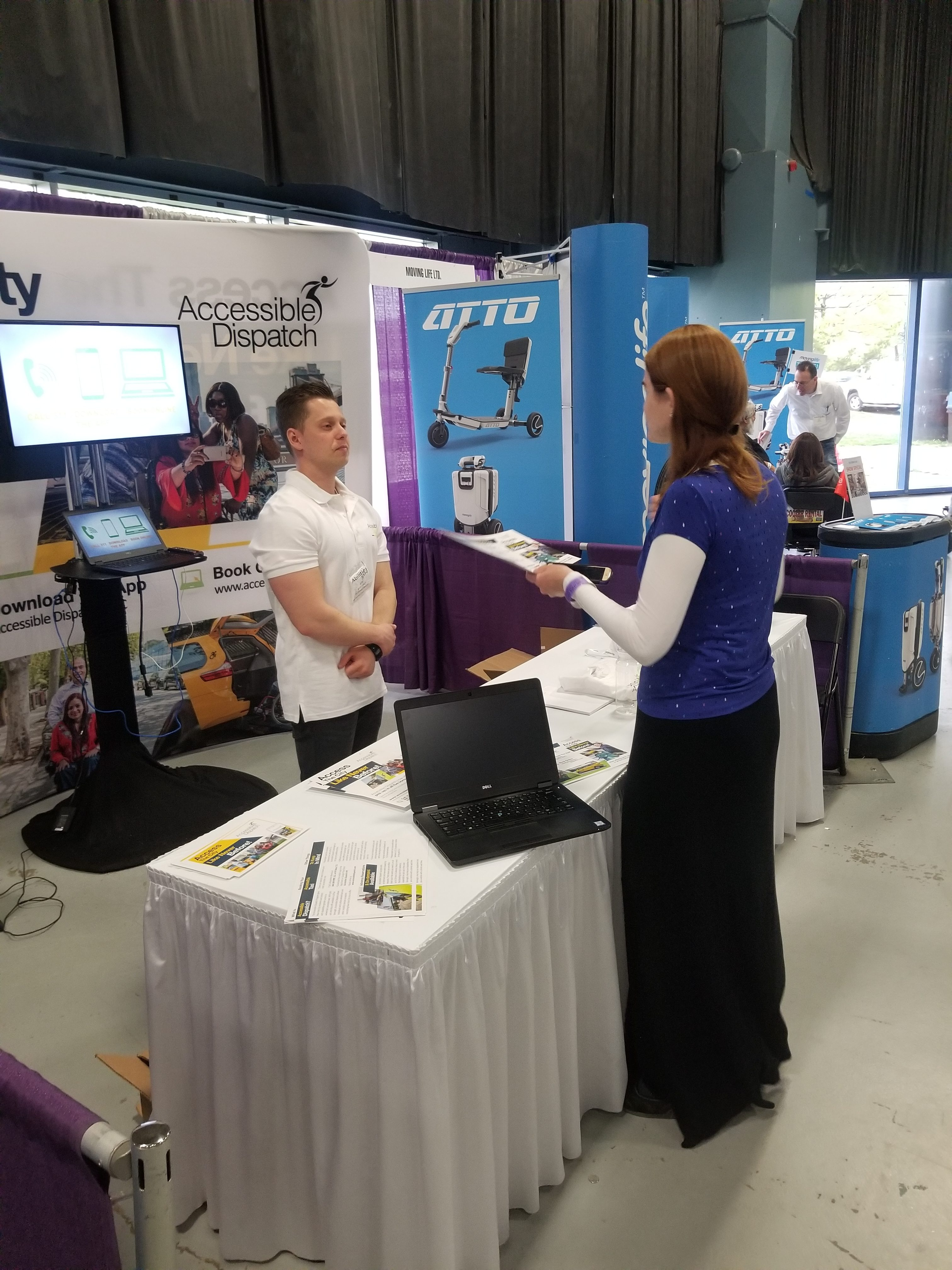 An attendee of the 2018 abilities expo speaking with a team member of the Accessible Dispatch program