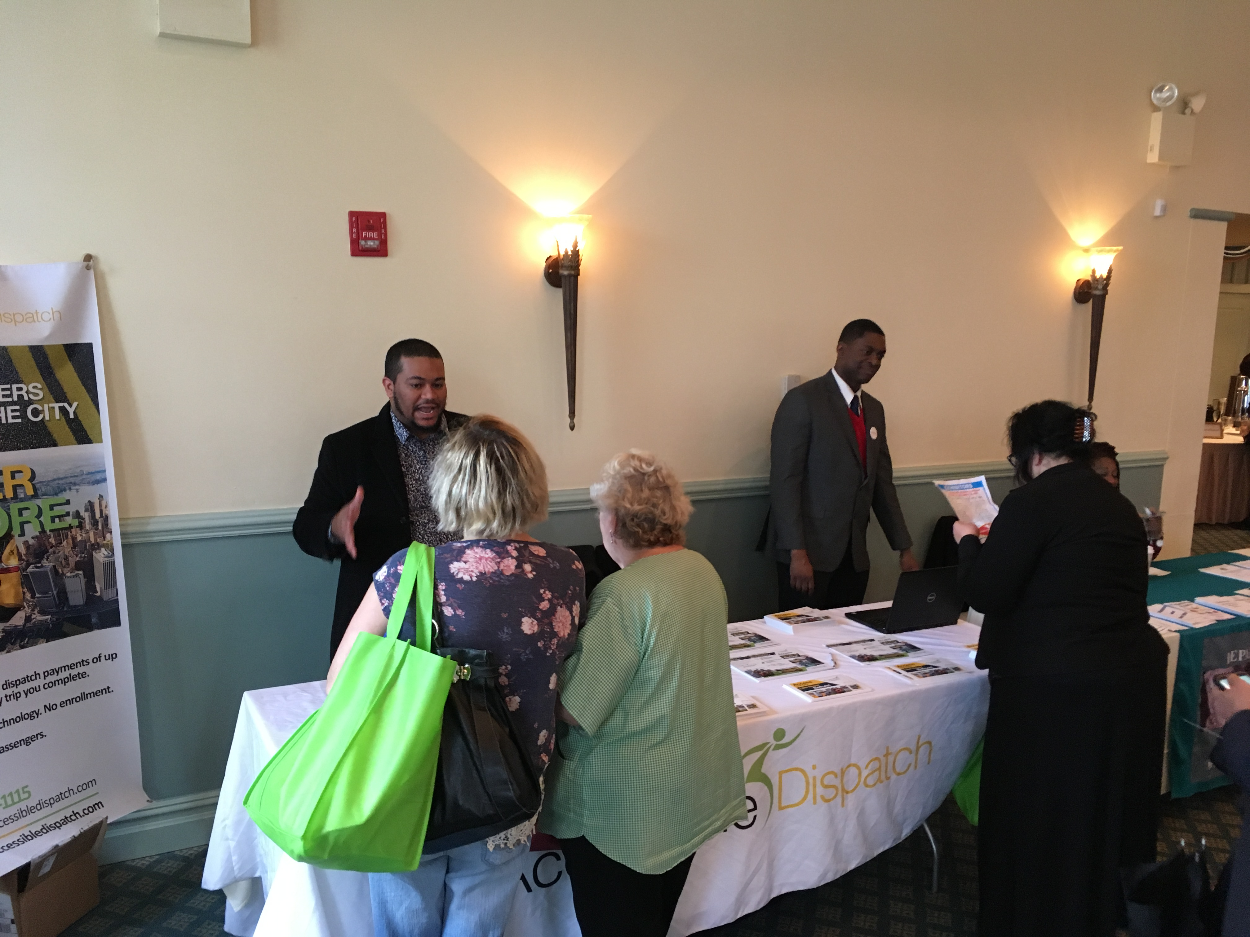TLC Accessible Dispatch NYC outreach team members explaining the benefits of the Accessible Dispatch program to seniors at health expo