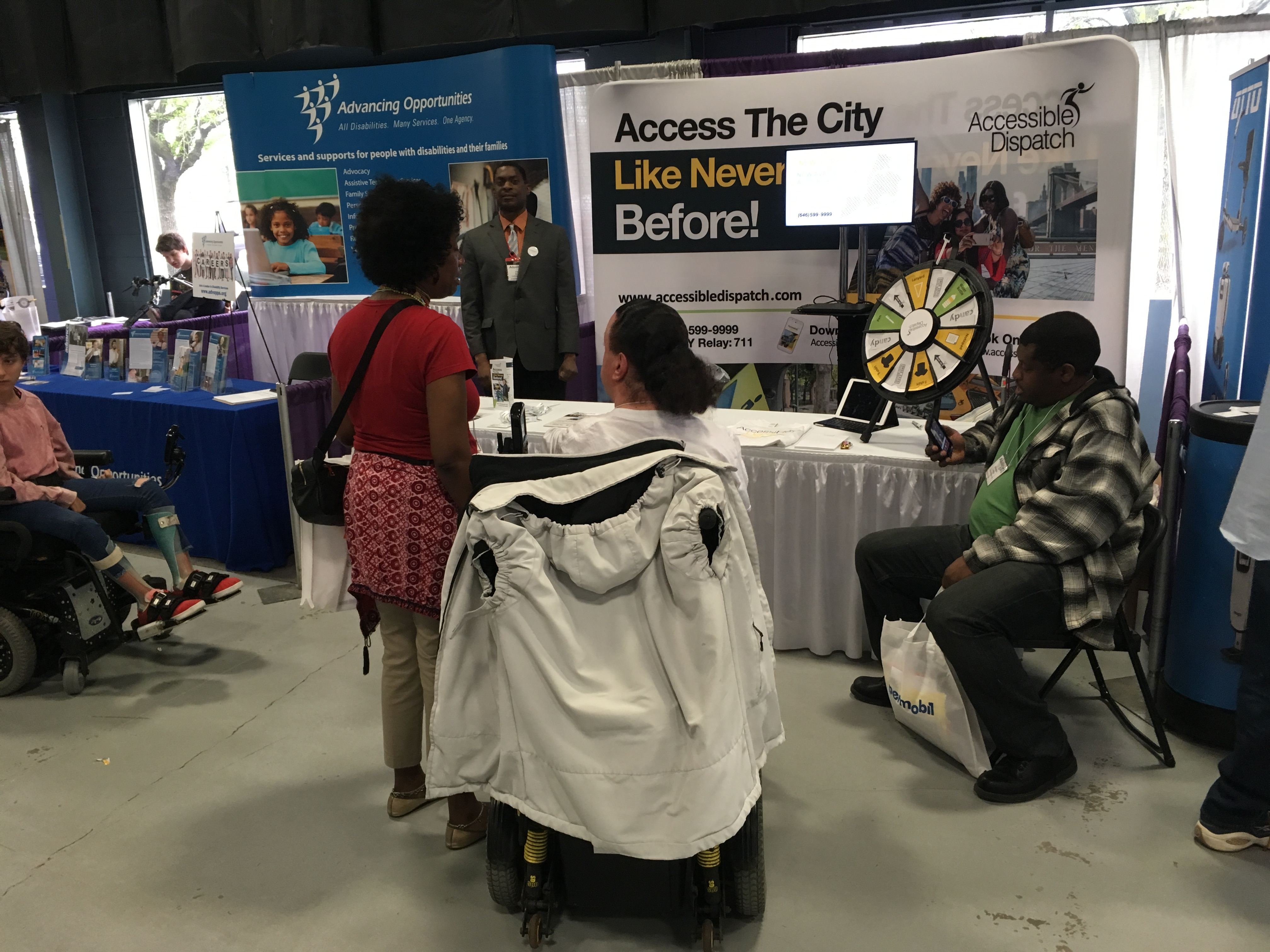 2018 abilities expo attendee standing in front of the Accessible Dispatch booth and speaking with one of the program's dispatchers