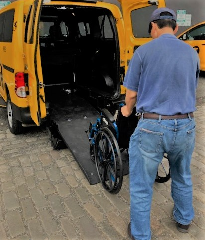 A taxi driver is at a training course. He is learning how to secure a wheelchair into his wheelchair accessible taxi.