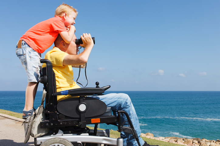 Father who utilizes a wheelchair looking through binoculars while his young boy stands behind him while hugging him looking in the distance.