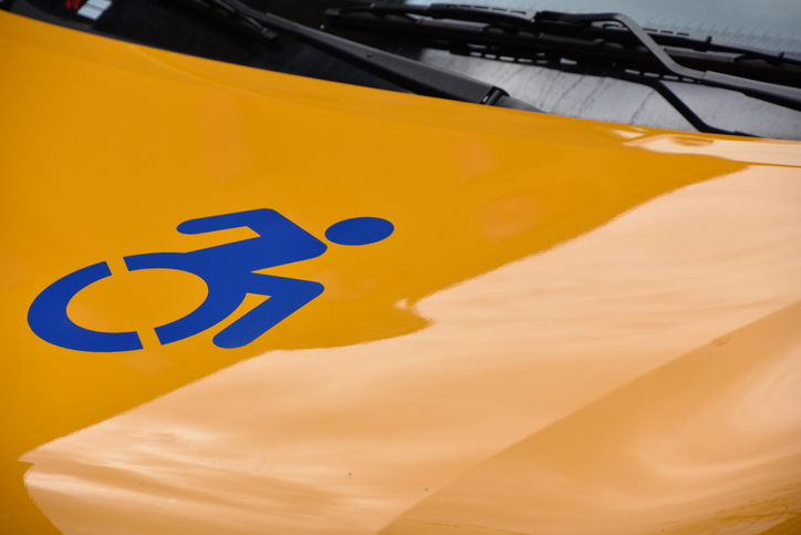 Close up shot of a wheelchair accessibility symbol on a yellow taxi.