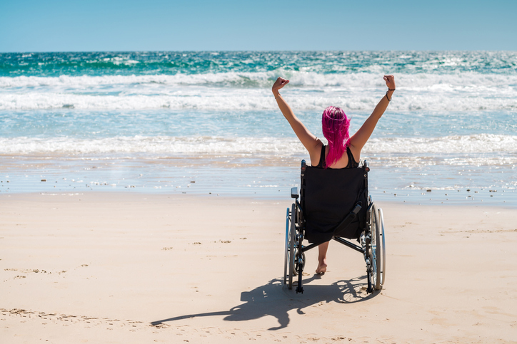 Young woman in the wheelchair at the beach enjoying fresh air with her arms wide open.