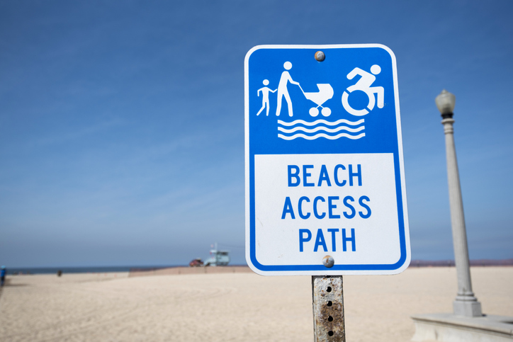 Sign board indicating mobility device accessible path at the beach