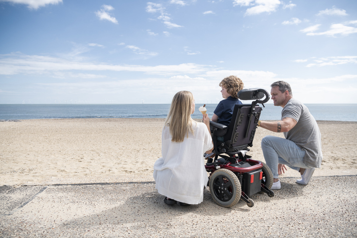 Mother and father kneeling by child, who is in wheelchair by the beach, enjoying an ice cream while looking at the waves.