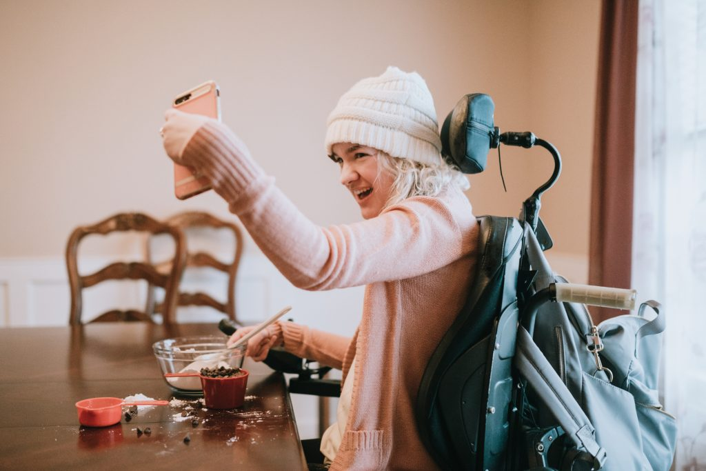 • A young woman in a wheelchair takes a selfie with her smartphone while mixing together ingredients for making chocolate chip cookies.