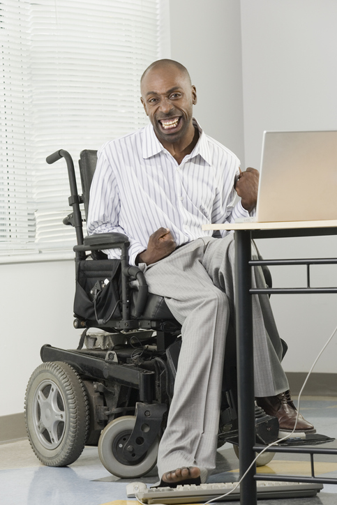 • Image of a businessman with Cerebral Palsy sitting in a wheelchair and working on a computer with his foot