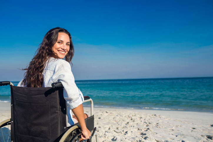 A young woman in wheelchair at the beach is looking back in to the camera and smiling
